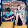 Two children devour the books they are reading and simply ignore the slide upon which they sit. A good book will transform young minds, create a lifelong love for learning. Summer reading programs at local libraries are the best way to keep kids engaged i